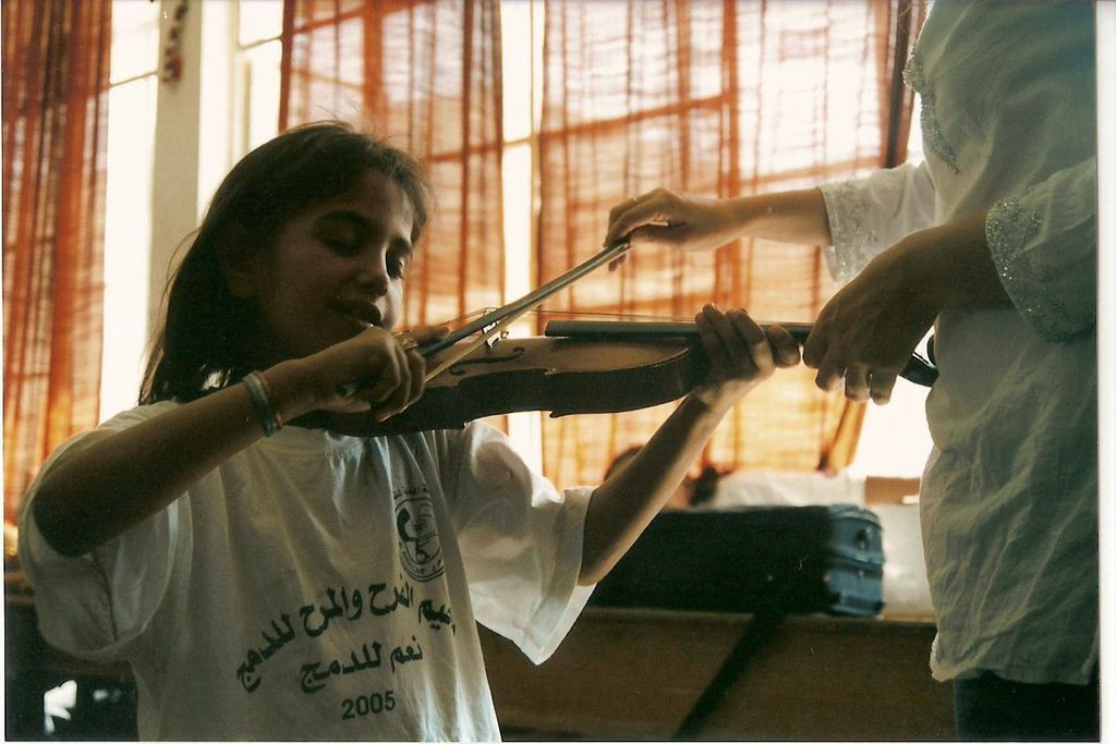 An Al Kamandjati student learns the violin, Al Amari Palestinian refugee camp.  Photo by Margarida Mota.