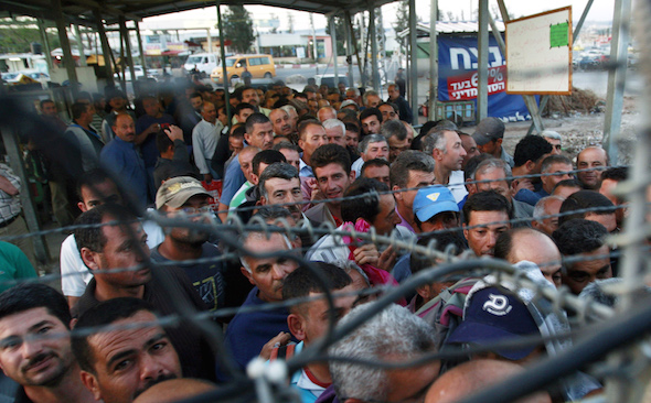 Palestinian workers wait to cross at the Israeli checkpoint in Jalameh, south of the West Bank city of Jenin, on their way to work in Israel. (Mohammed Ballas / AP)